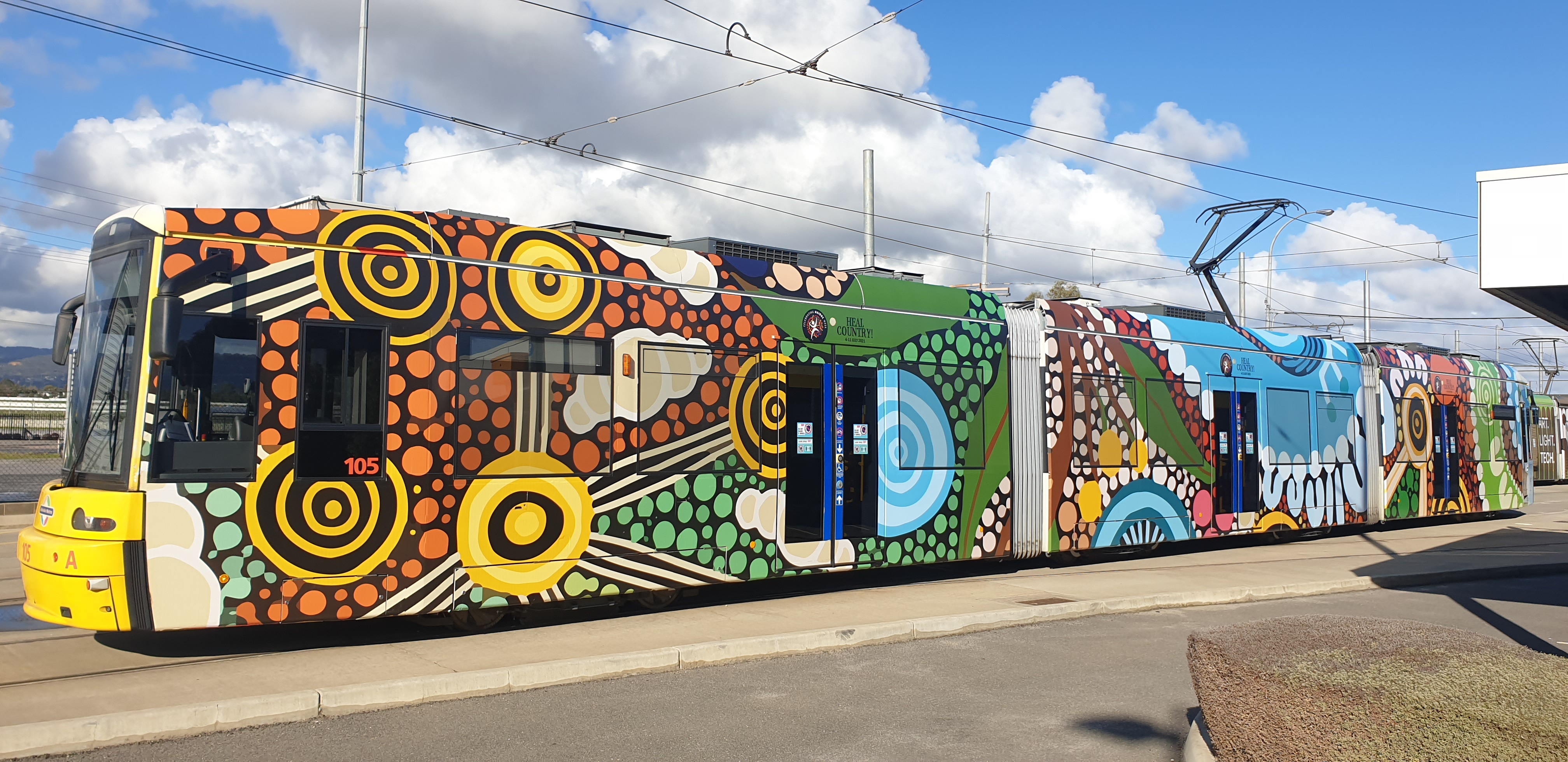 The Adelaide Metro NAIDOC Week tram is wrapped in the artwork of the 2021 National NAIDOC Poster, titled 'Care for Country'.