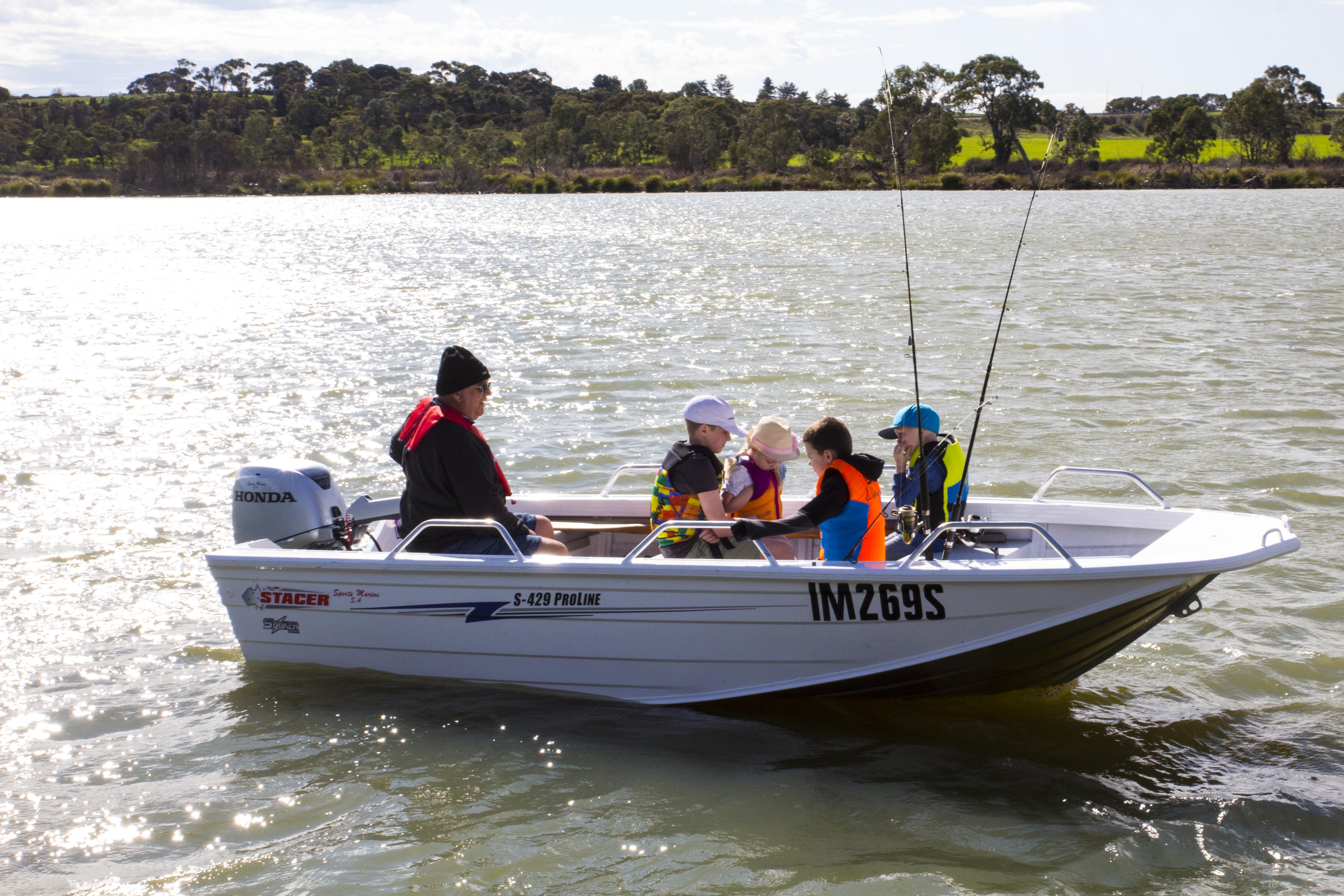 A small boat on the water. Passengers include one adilt and five childre. All are waering life jackets and there are three fishing rods visible.