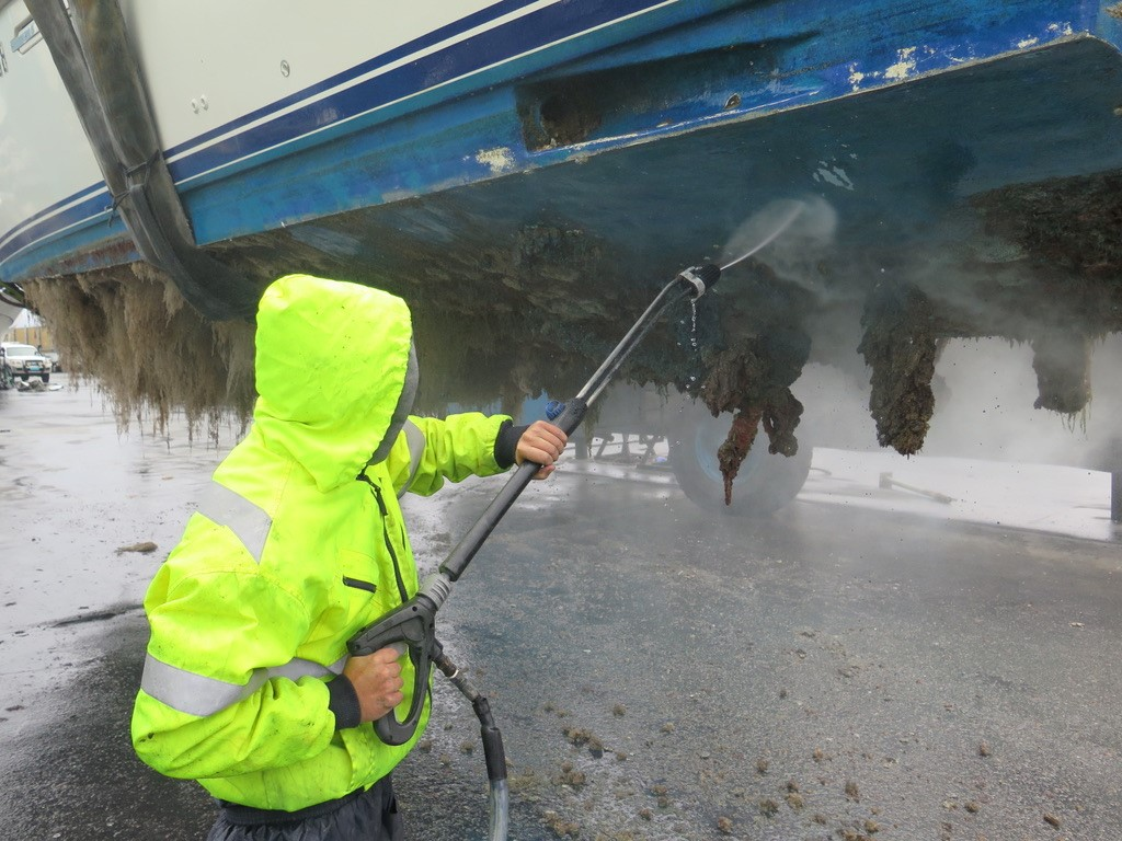 Man with high pressure water hose cleaning the bottom of a yacht
